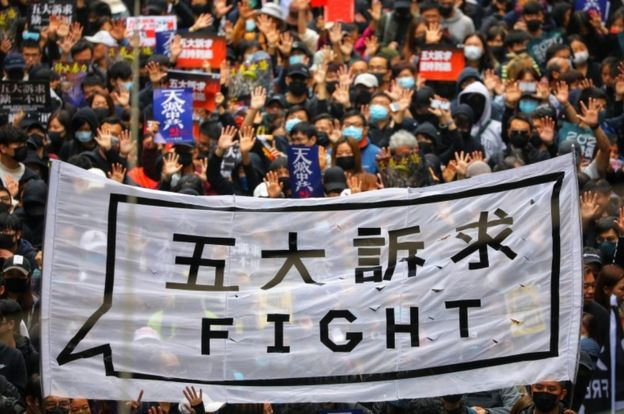 """People hold a banner reading """"Fight"""" as they take part in an anti-government rally on New Year's Day in Hong Kong"""